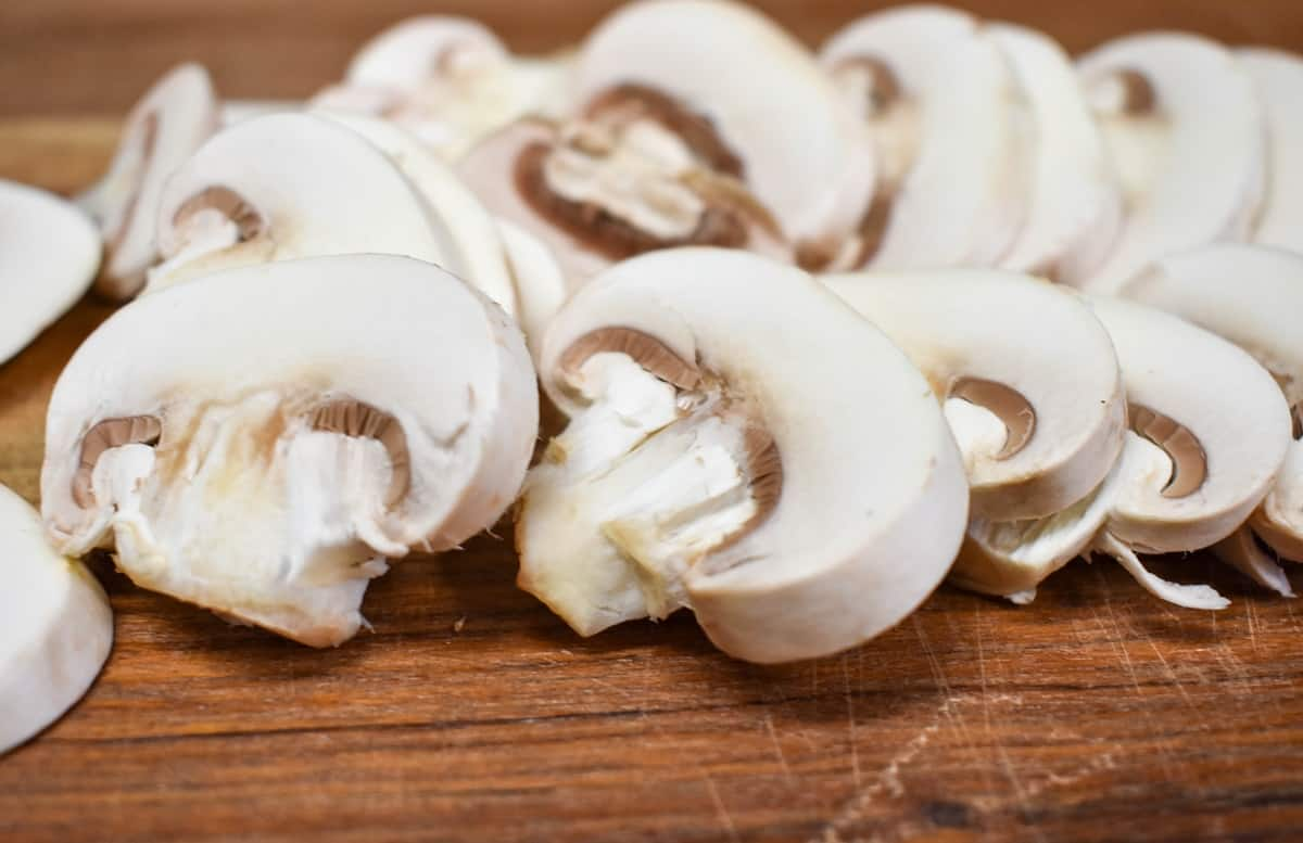 A close-up image of sliced white button mushrooms on a wood cutting board.