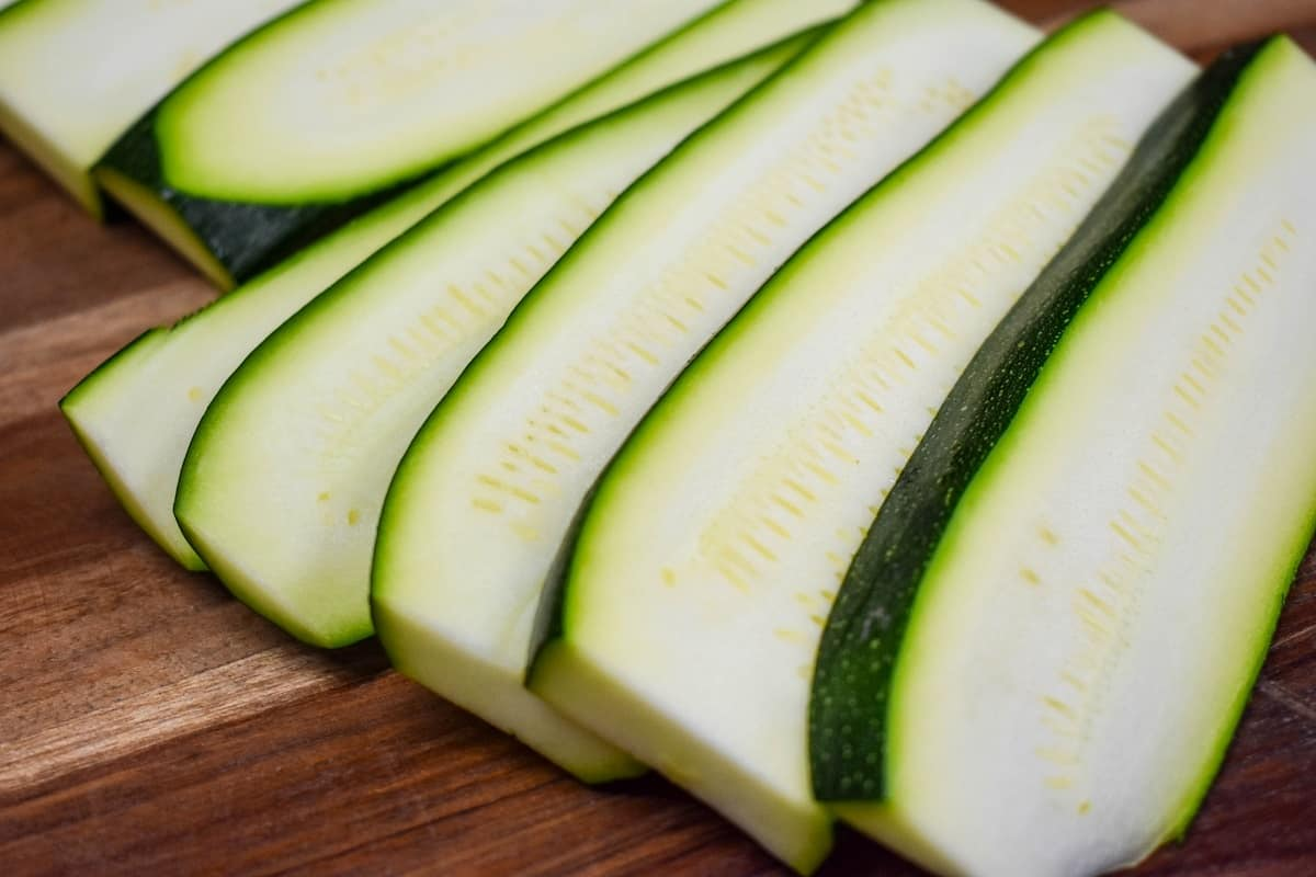 Sliced, uncooked zucchini fanned out on a wood cutting board.