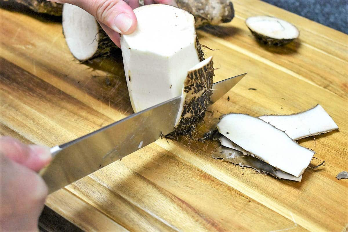 An image of a hand holding and peeling a malanga with a large knife on a wood cutting board.