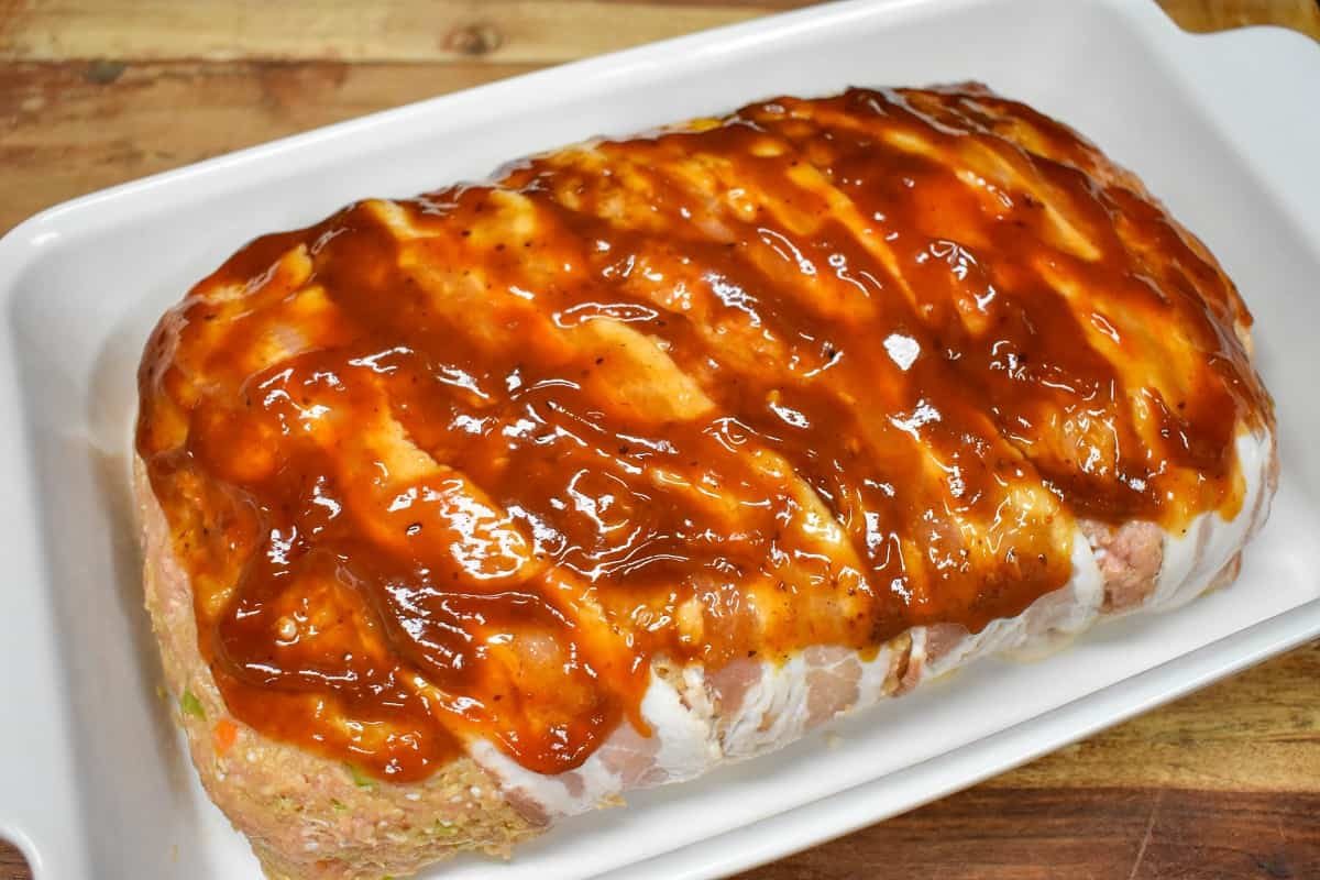 An image of the loaf with the ketchup and steak sauce glaze before baking in a white casserole dish.