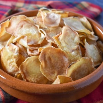 Malanga chips in a terracotta bowl on a red, plaid linen.