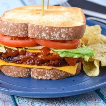 The meatloaf sandwich served on a blue plate with potato chip.s arranged on its sides