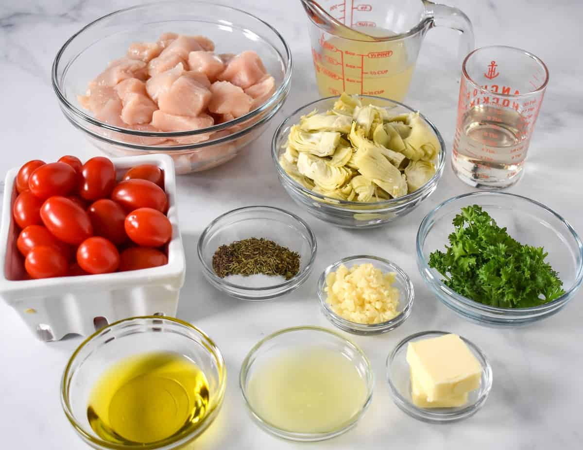 The prepped ingredients for the dish separated in glass bowls and arranged on a white table.