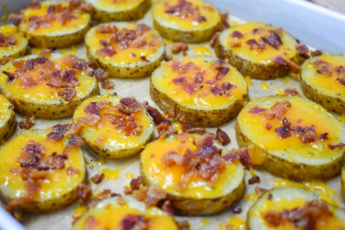 The baked potato slices arranged on a parchment paper lined baking sheet.