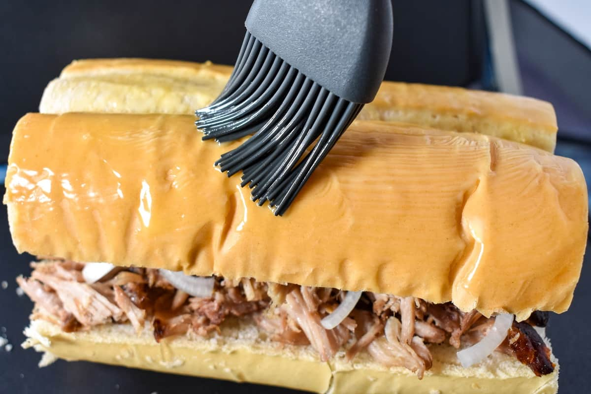 A gray silicone brush applying melted butter on the sandwich.