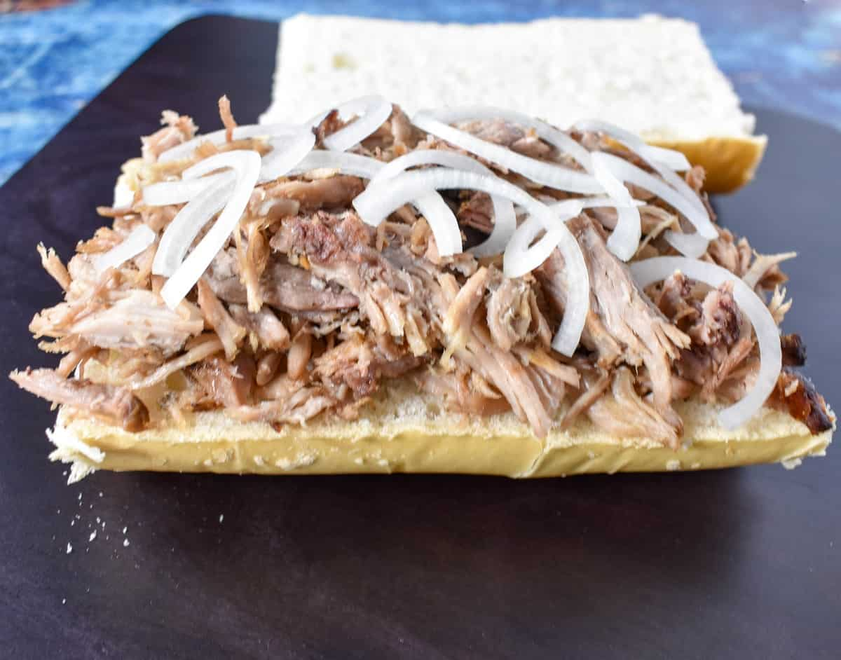 A generous amount of shredded roast pork topped with thin sliced onions on the bottom half of Cuban bread. The top part is in the background.