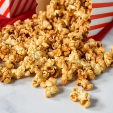 Caramel popcorn spilled on a white table from a small, red and white striped container.