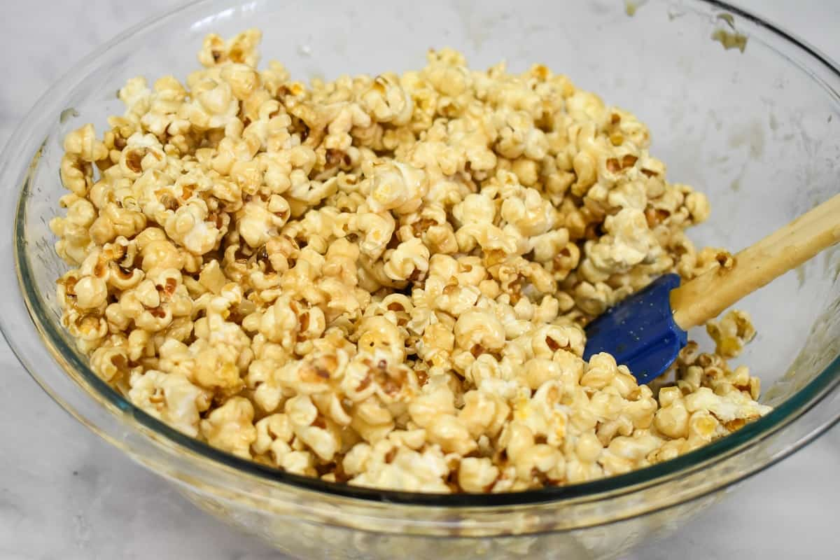 The popcorn coated with the caramel in a large, glass bowl with a blue silicone spatula on the right.