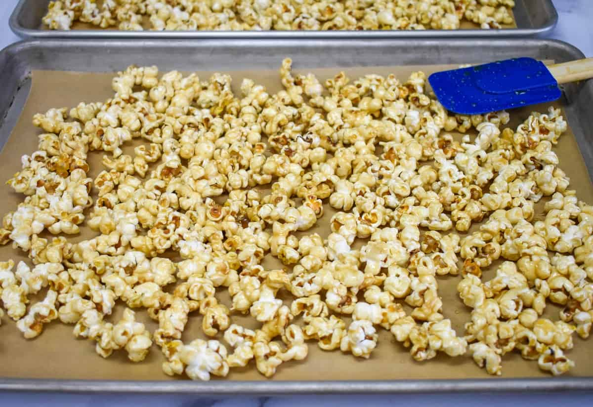 An image of the caramel corn spread on a large baking sheet with a blue rubber spatula.