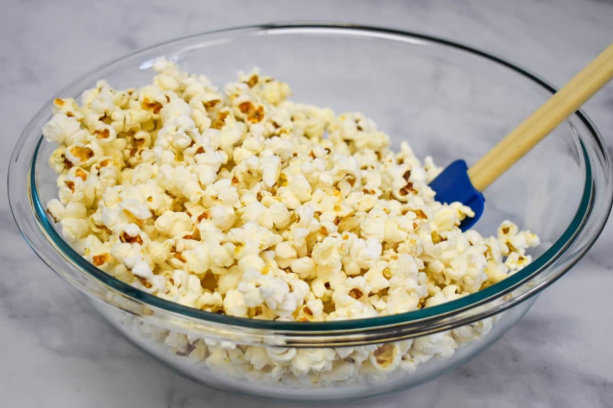 Popcorn in a large, glass bowl with a blue silicone spatula in the bowl to the right.