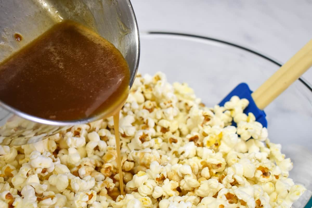 An image of pouring caramel sauce from the saucepan into the large, glass bowl with the popcorn in it.