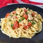 The artichoke chicken served on a bed of linguine noodles on a large black plate set on a red linen with a fork and knife in the background.
