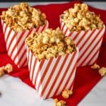Three red and white striped containers filled with the caramel corn displayed on a red linen on a white table.