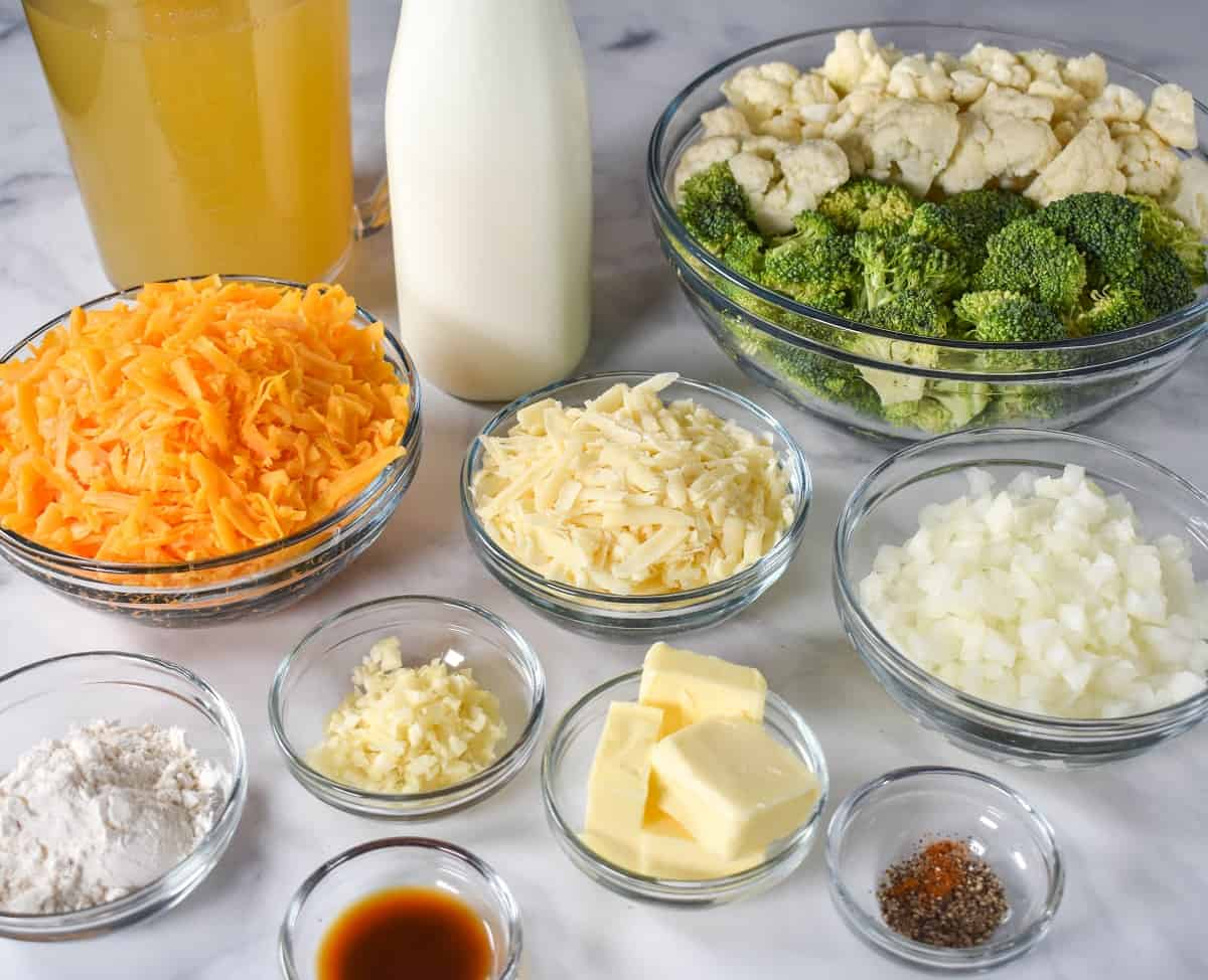 The prepped ingredients for the soup separated in clear bowls and arranged on a white table.