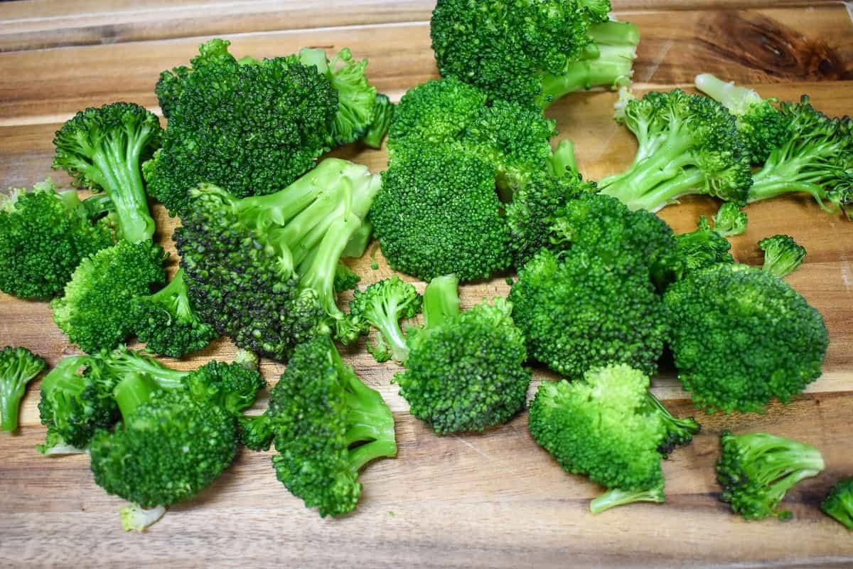 Broccoli florets on a wood cutting board.