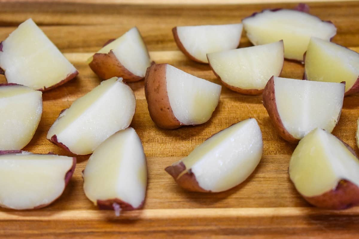 Cooked quartered red potatoes on a wood cutting board.