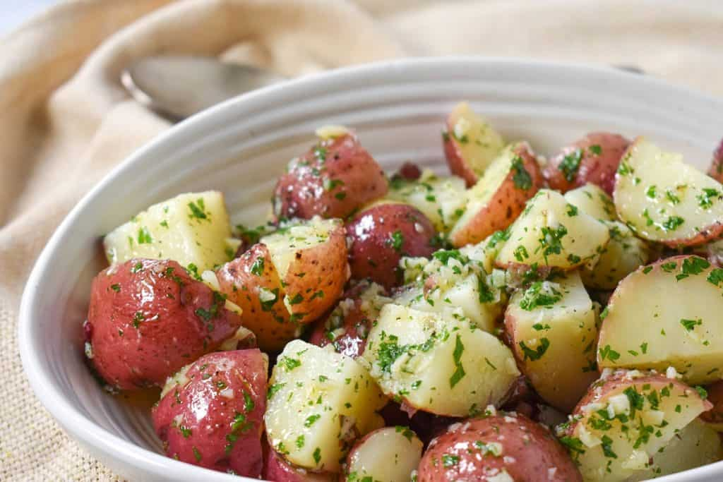 The finished garlic parsley potatoes served in a white bowl on a beige linen with a serving spoon in the background.
