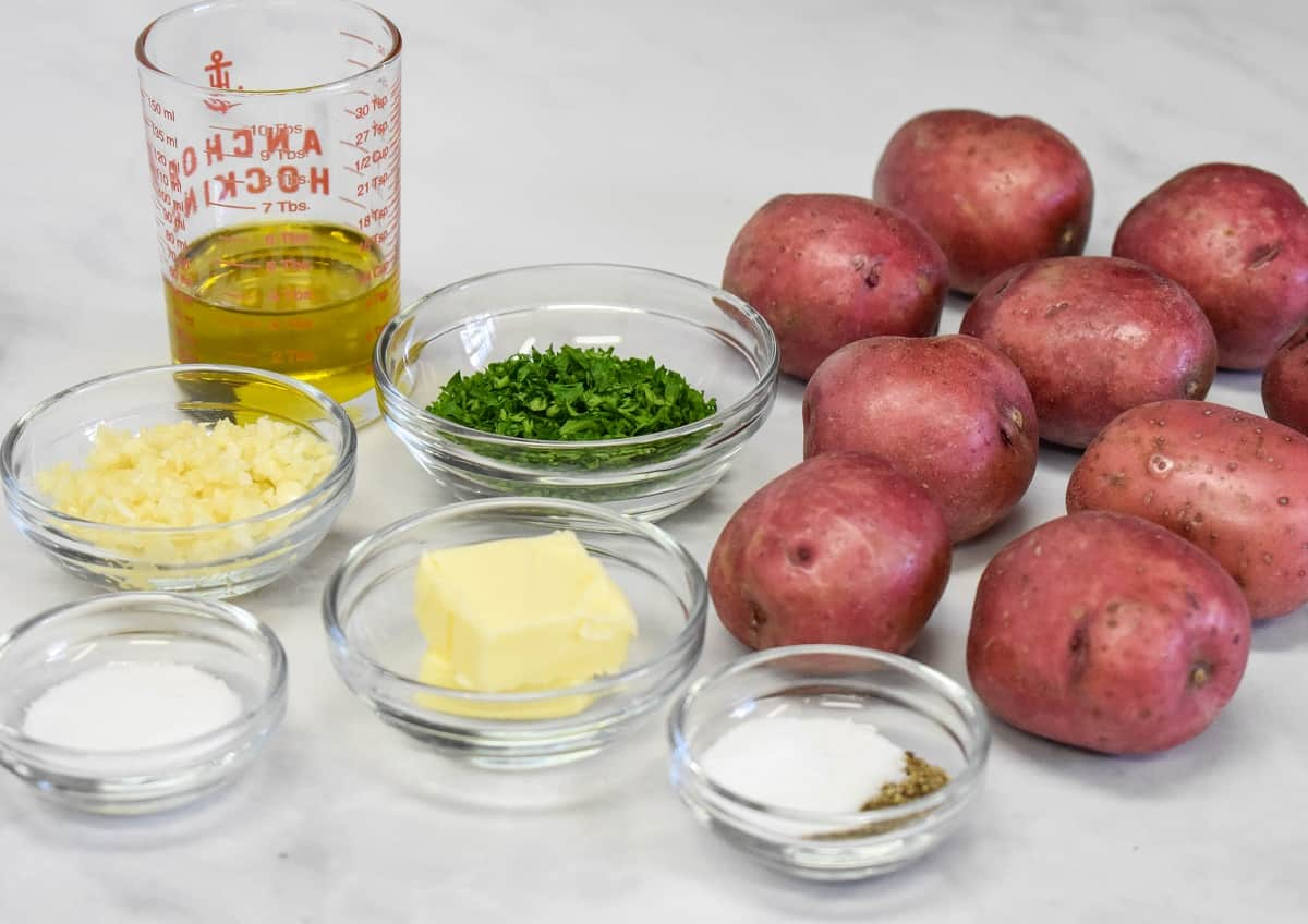 The ingredients for the potatoes prepped and separated into glass bowls with the whole red potatoes to the right side.