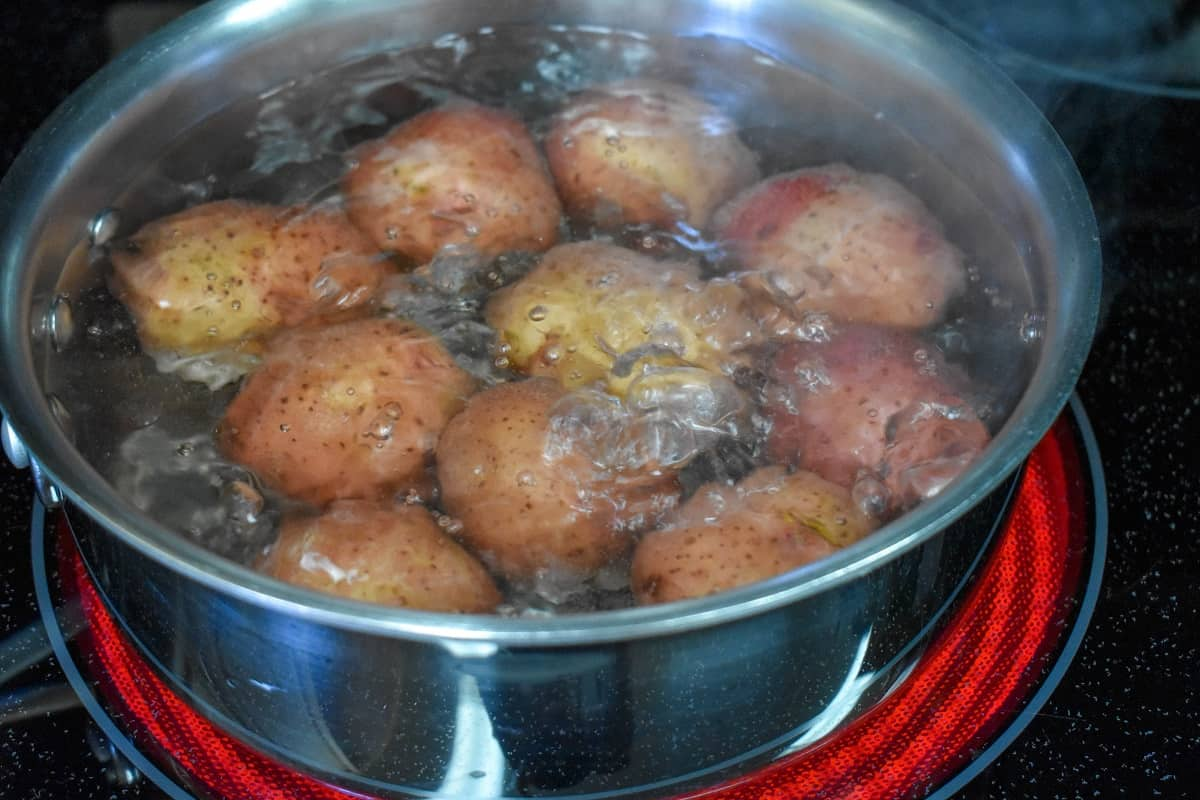 Red potatoes boiling in a pot on a glass top stove.