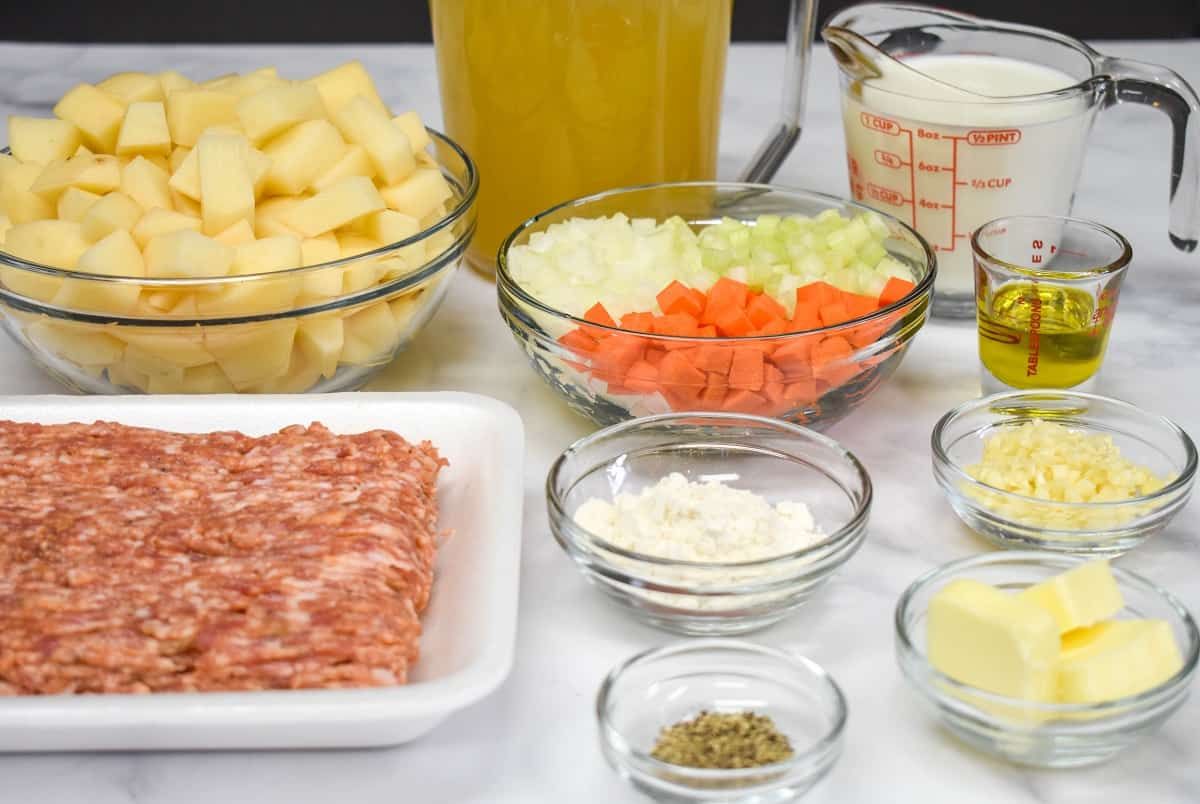The ingredients for the soup, prepped and separated in glass bowls all arranged on a white table.