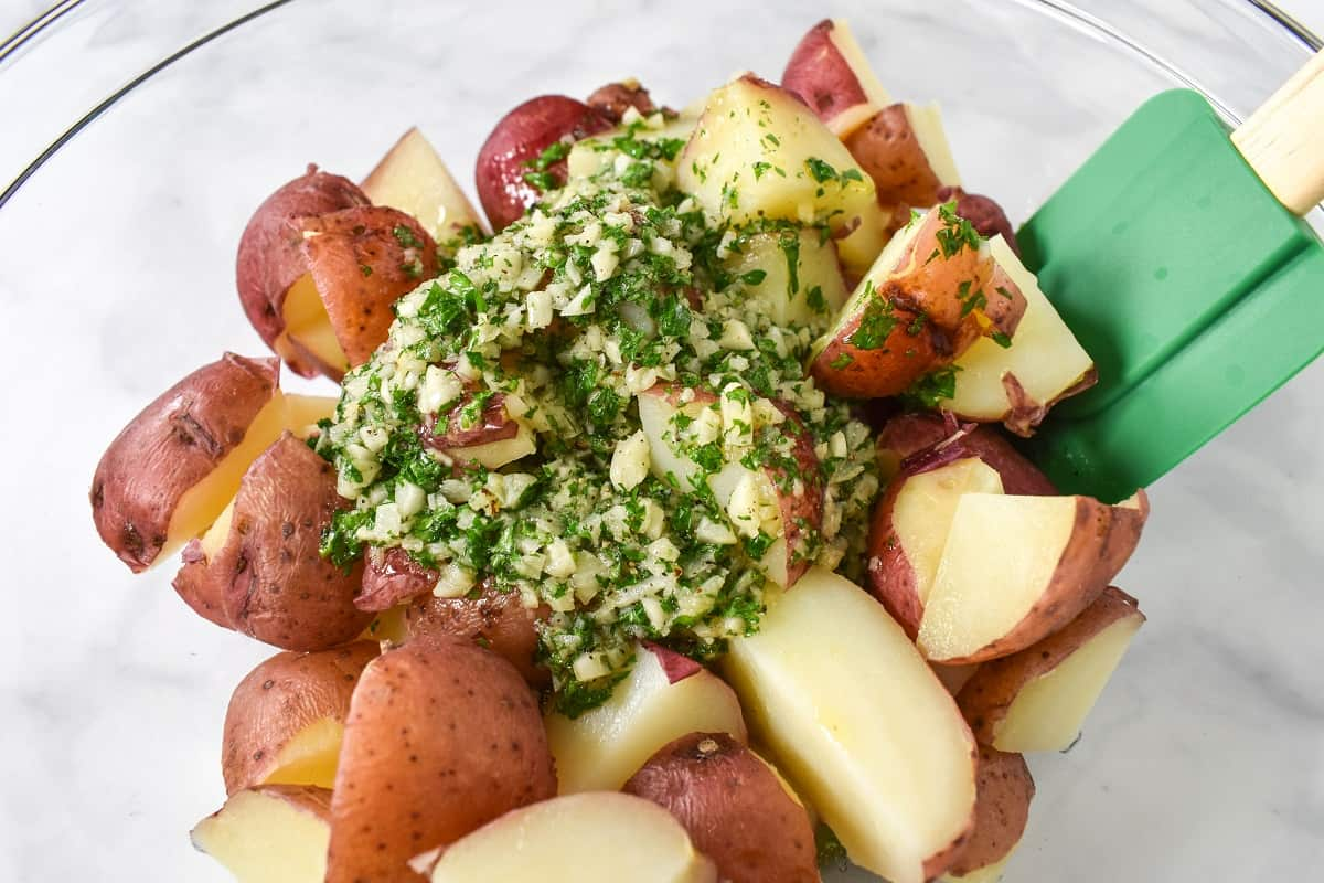 Cut red potatoes in a large, clear bowl with the garlic parsley sauce on top and a green rubber spatula to the right side.