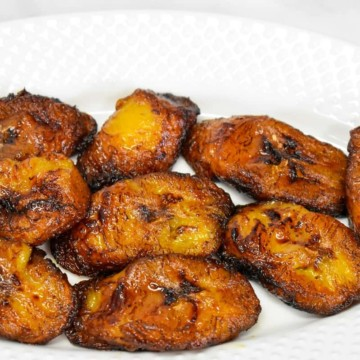 The fried plantains arranged on a white plate with parsley as a garnish on the left side.