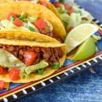 Two tacos in a hard shell topped with lettuce and tomatoes displayed on a colorful plate on a blue table.