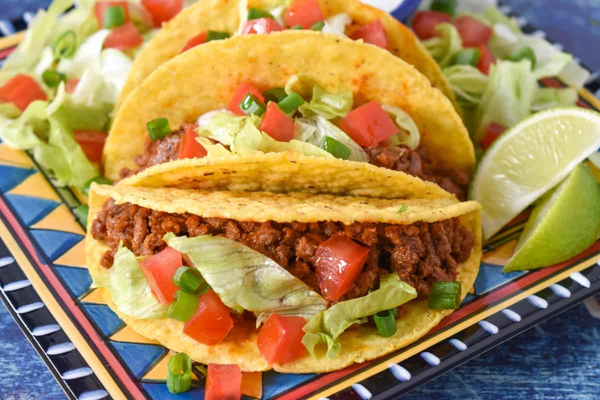 The ground beef in hard shell tacos topped with diced tomatoes, lettuce and green onions served on a colorful plate and set on a blue table.