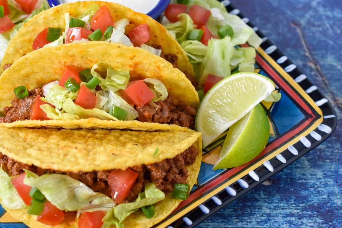 Three tacos topped with lettuce, tomato and green onions displayed on a colorful plate with two lime wedges to the right and set on a blue table.