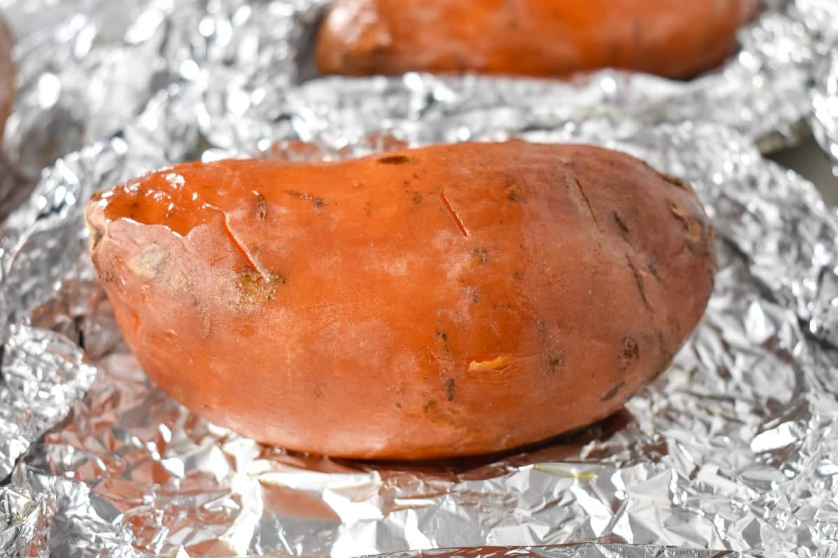 A baked sweet potato sitting on the foil it was wrapped in.
