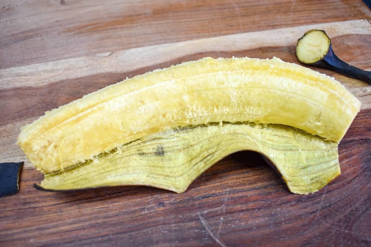 A half peeled ripe plantain on a wood cutting board.