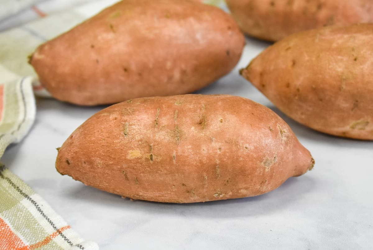 Four sweet potatoes arranged on a white table with a light colored kitchen towel on the left side.