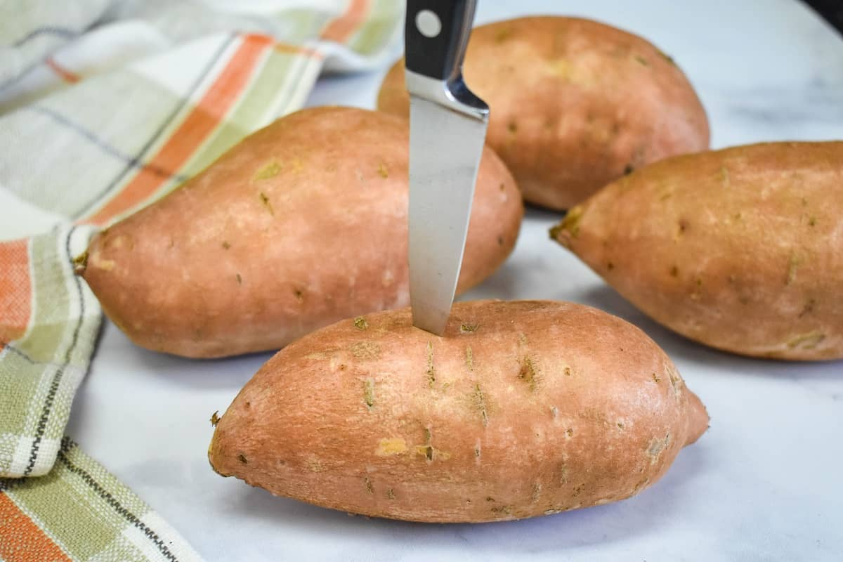 Four sweet potatoes on a white table the one in the forefront is being pricked with a paring knife.