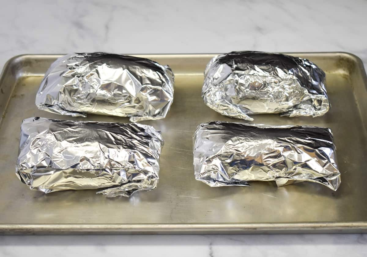 Four sweet potatoes wrapped in foil and arranged on a baking sheet.