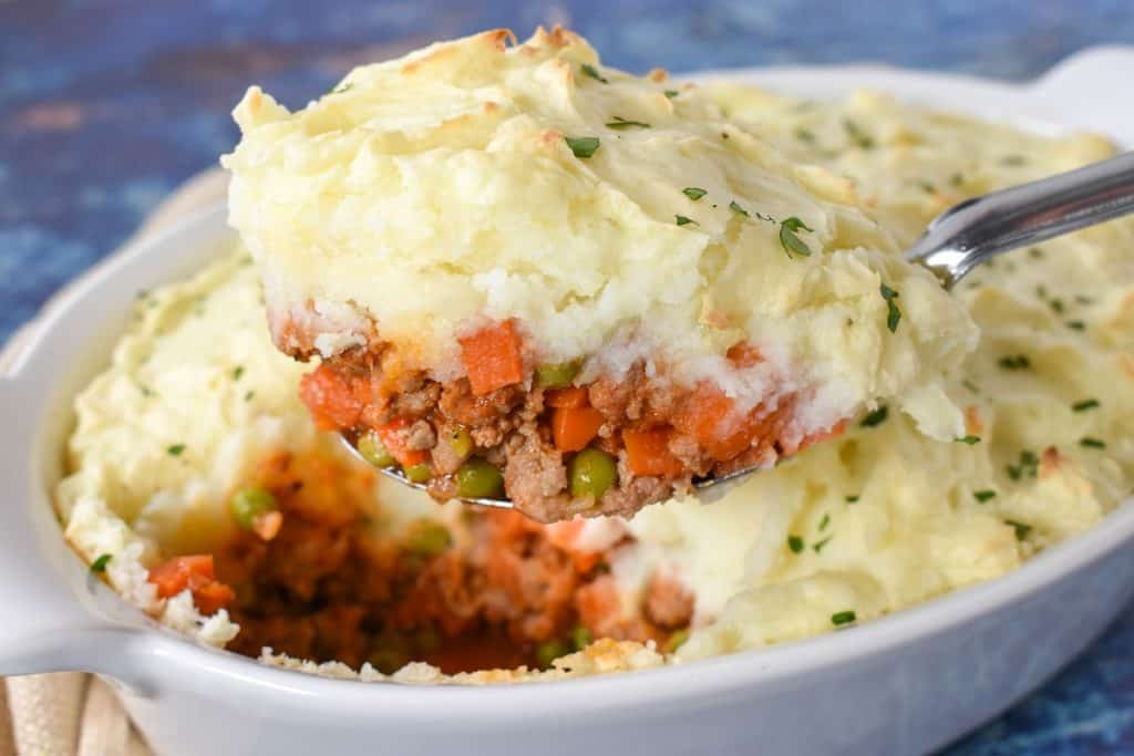A serving spoon lifting a serving of shepherd's pie out of a white casserole dish.