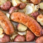 A close up of the baked sausage with potatoes on the sheet pan.