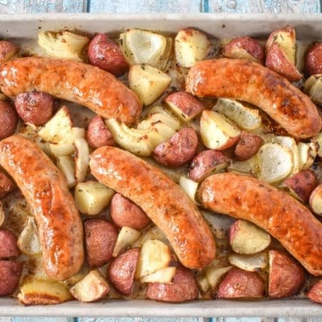 An image of five Italian sausages cooked on a sheet pan with quartered red potatoes and onions.