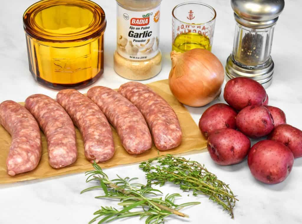 The ingredients for the baked Italian sausage and potatoes arranged on a white table.