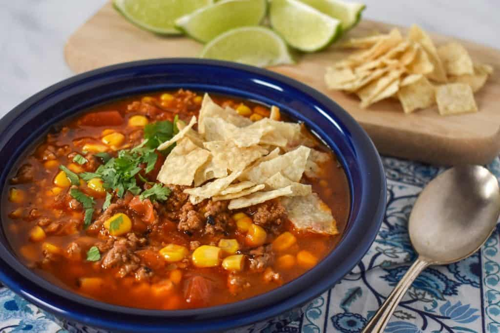 The soup served in a blue plate and displayed on a blue and white linen with lime wedges and extra tortilla chips in the background.