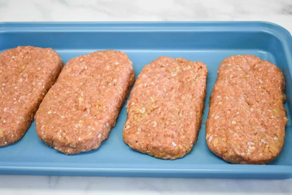 Four formed Salisbury steak patties arranged on a light blue tray.