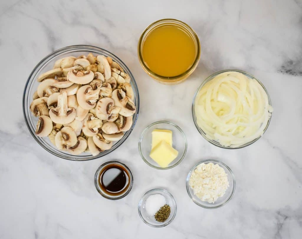 The ingredients for the mushroom gravy separated in glass bowls and displayed on a white table.