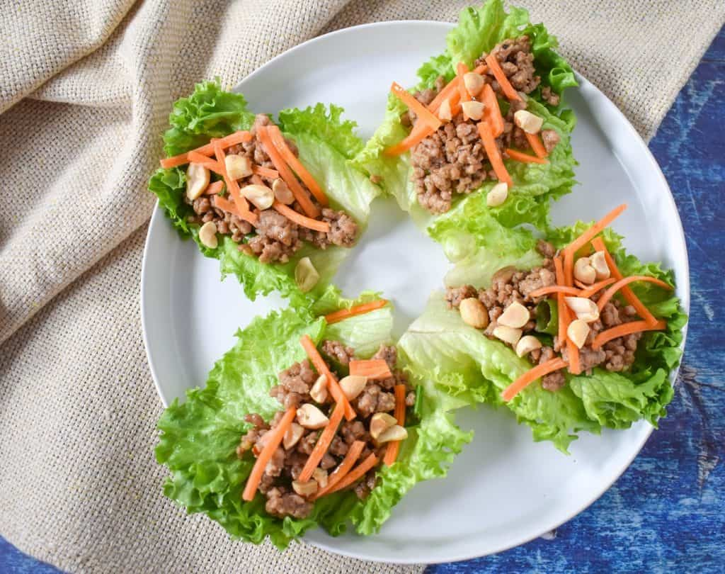 Four prepared lettuce cups served on a white plate and set on a beige linen on a blue table.