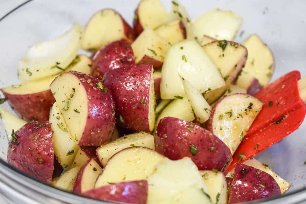 The potatoes and onions mixed with the seasoning in a large glass bowl.