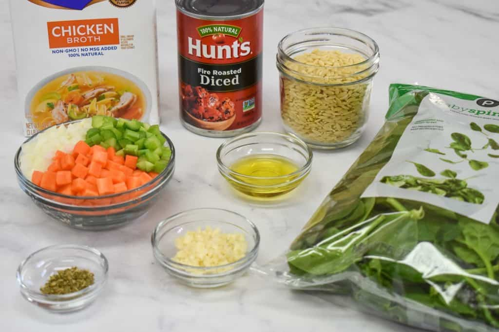 The prepped ingredients for the soup arranged on a white table.