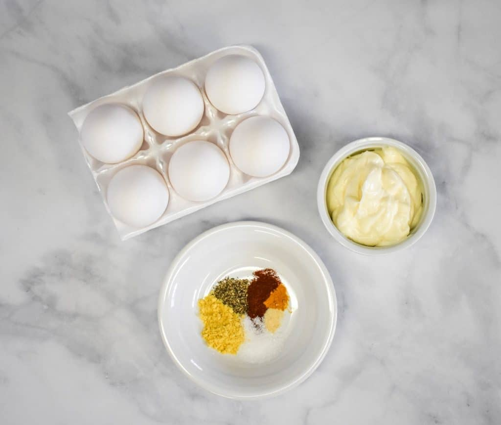 The ingredients for the egg salad arranged on a white table. The spices are displayed on a small white plate.