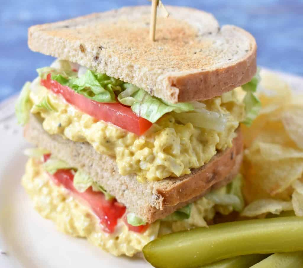 A stacked egg salad sandwich with lettuce and tomatoes on a white plate with chips and pickle spears on the side.