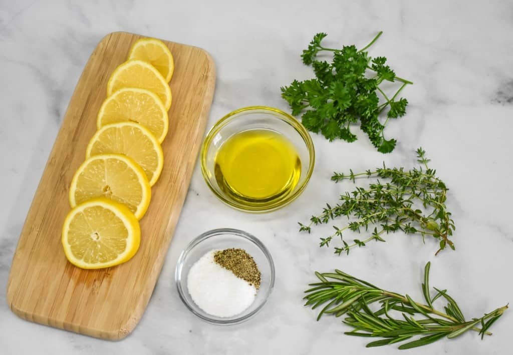 Lemon slices, herbs, olive oil, salt and pepper arranged on a white table. The lemons are displayed on a small wood cutting board.