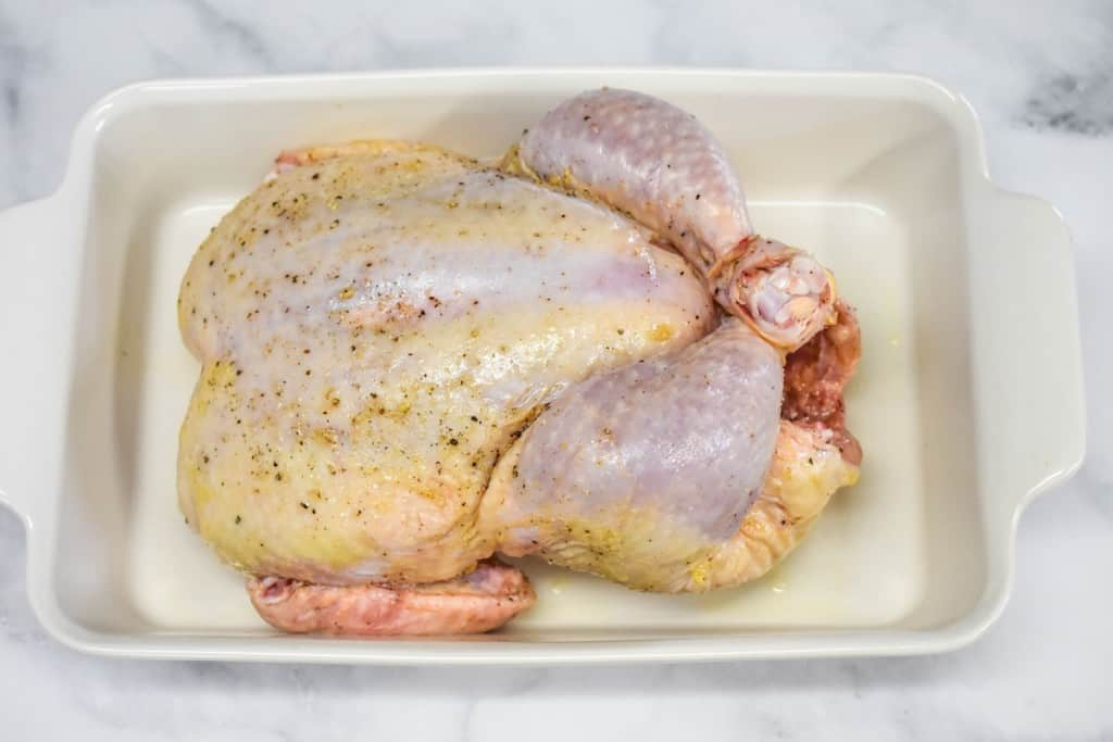 A raw, whole chicken in a white casserole dish set on a white table.