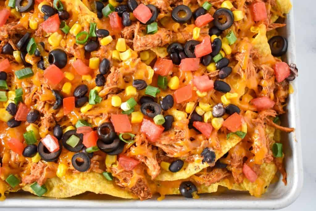 An image of the finished shredded chicken nachos on a sheet pan.