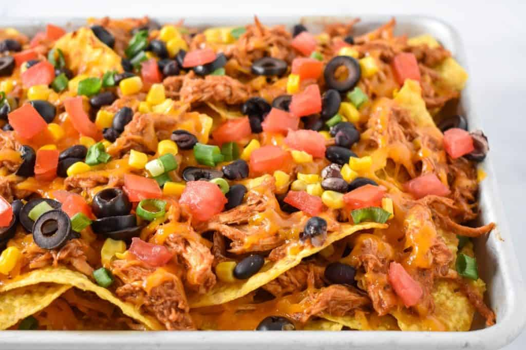 A close up of the nachos on a sheet pan.